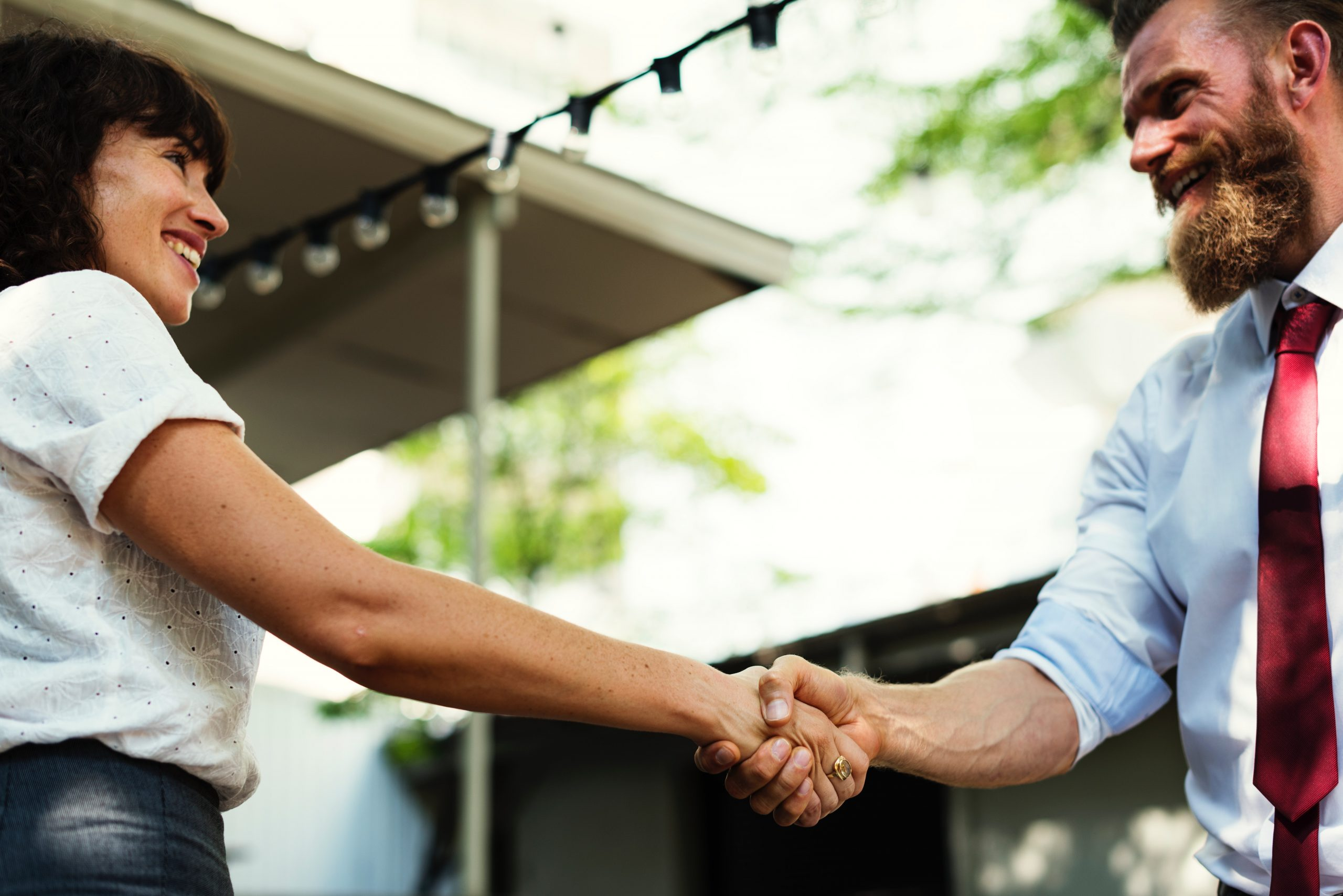 Woman and Man Shaking Hands Outdoors
