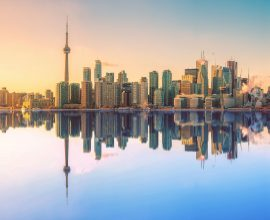 The Toronto city skyline is mirrored by the lake.